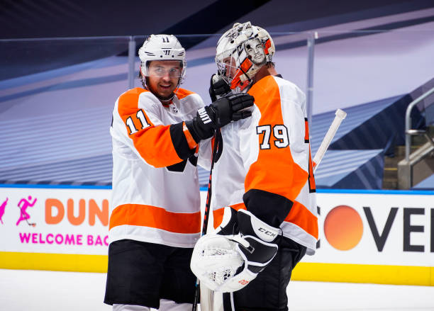 Travis Konecny and Carter Hart of the Philadelphia Flyers celebrate after defeating the Boston Bruins in a Round Robin game during the 2020 NHL...