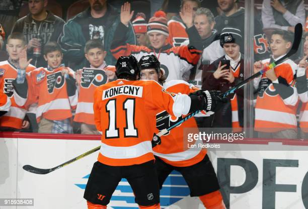 Travis Konecny and Nolan Patrick of the Philadelphia Flyers check each other into the boards in front of their fans during warmups prior to their...