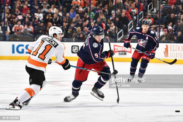 Travis Konecny of the Philadelphia Flyers and Artemi Panarin of the Columbus Blue Jackets skate after a loose puck during the first period of a game...
