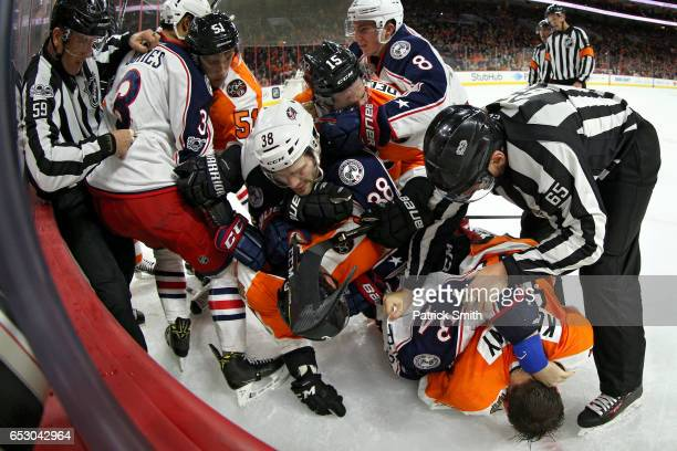 Travis Konecny of the Philadelphia Flyers and Josh Anderson of the Columbus Blue Jackets push and shove as teammates hold one another during the...