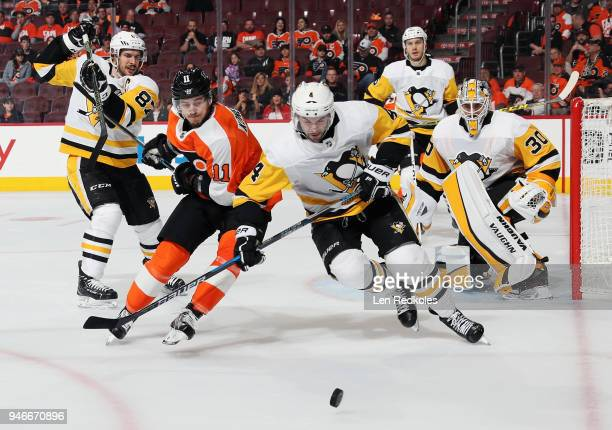 Travis Konecny of the Philadelphia Flyers battles for the loose puck with Justin Schultz of the Pittsburgh Penguins in Game Three of the Eastern...