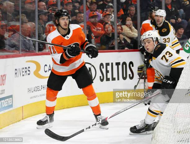 Travis Konecny of the Philadelphia Flyers completes a pass against Charlie McAvoy of the Boston Bruins on March 10 2020 at the Wells Fargo Center in...