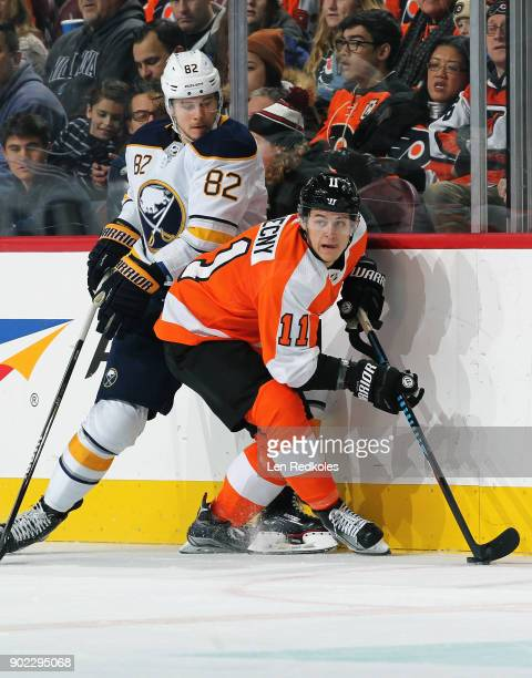 Travis Konecny of the Philadelphia Flyers controls the puck and looks to make a pass while battling along the boards with Nathan Beaulieu of the...