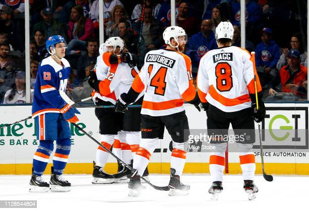 Travis Konecny of the Philadelphia Flyers is congratulated by his teammates after scoring a first period goal as Mathew Barzal of the New York...
