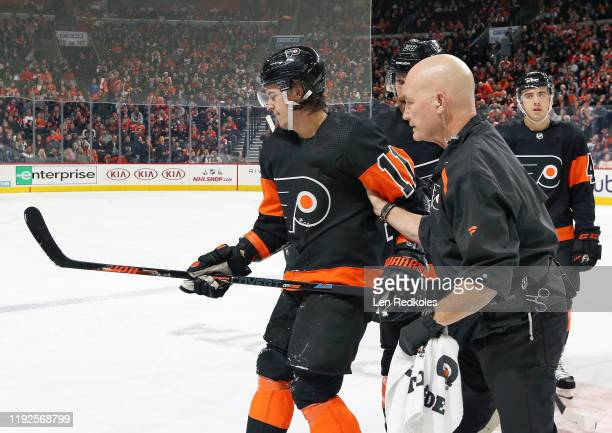 Travis Konecny of the Philadelphia Flyers is helped off the ice by the teams Director of Sports Medicine Jim McCrossin following a center ice...