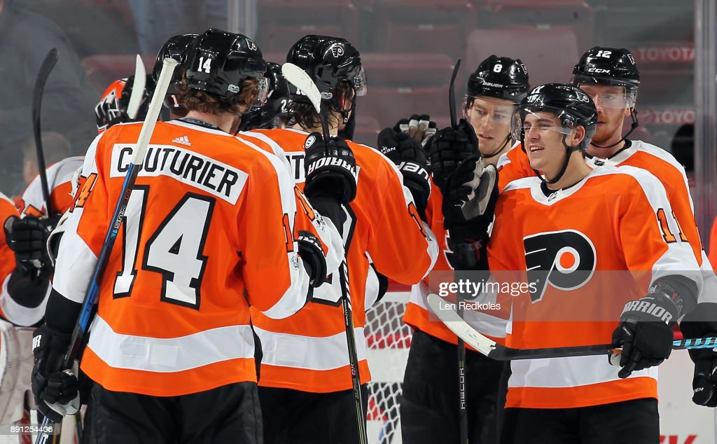 Travis Konecny #11 of the Philadelphia Flyers, playing in his 100th NHL game, celebrates with his teammates after defeating the Toronto Maple Leafs 4-2 on December 12, 2017 at the Wells Fargo Center in Philadelphia, Pennsylvania.