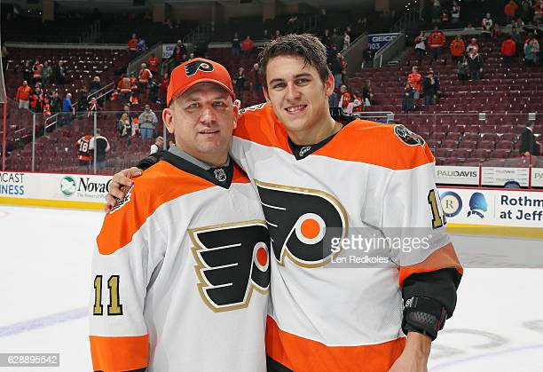 Travis Konecny of the Philadelphia Flyers poses for a photo with his father Rob after defeating the Chicago Blackhawks 31 on December 3 2016 at the...
