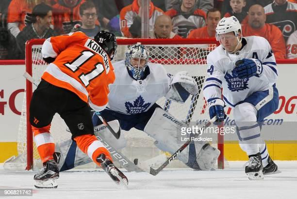Travis Konecny of the Philadelphia Flyers shoots the puck past Morgan Rielly of the Toronto Maple Leafs towards goaltender Frederik Andersen on...