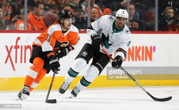 Travis Konecny of the Philadelphia Flyers skates the puck against Evander Kane of the San Jose Sharks on February 25, 2020 at the Wells Fargo Center...