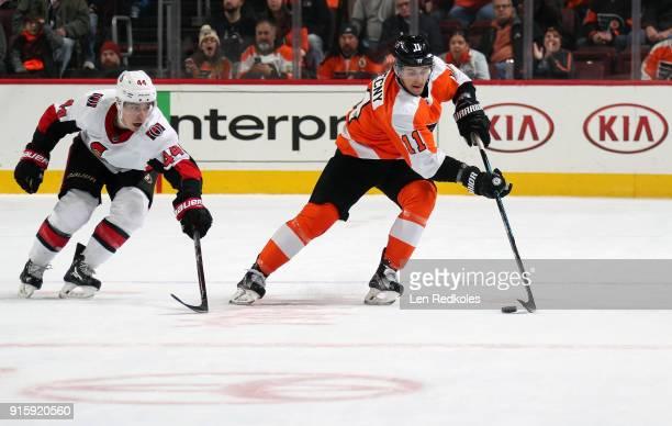 Travis Konecny of the Philadelphia Flyers skates the puck against JeanGabriel Pageau of the Ottawa Senators on February 3 2018 at the Wells Fargo...