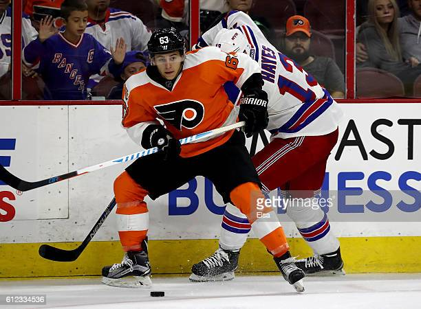 Travis Konecny of the Philadelphia Flyers tries to keep the puck from Kevin Hayes of the New York Rangers during a preseason game on October 3 2016...