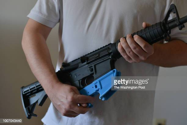 Travis Lerol holds an AR15 assault rifle along with a rifle's lower receiver made of ABS plastic that was constructed by his 3D printer at his home...