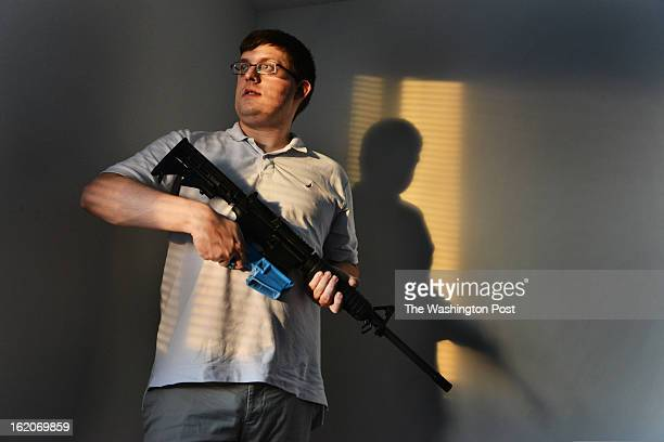 Travis Lerol holds an AR15 assault rifle that contains a bullet clip made of ABS plastic that was constructed by his 3D printer at his home on...