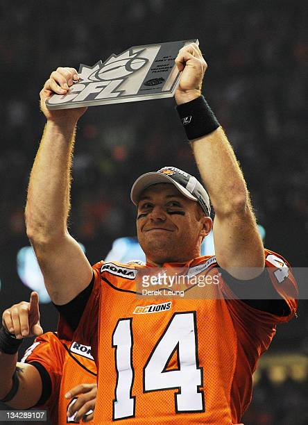 Travis Lulay of the BC Lions hoists the award for most valuable player after the game against the Winnipeg Blue Bombers during the Grey Cup at BC...