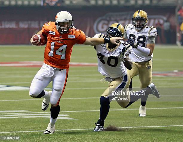 Travis Lulay of the BC Lions rushes upfield as he eludes the tackle of Odell Willis of the Winnipeg Blue Bombers during the CFL 99th Grey Cup...
