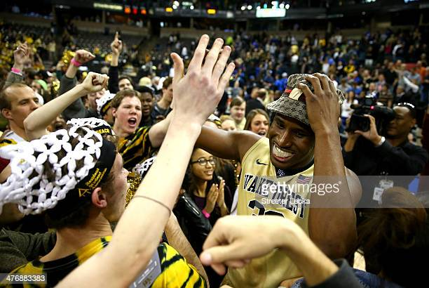 Travis McKie of the Wake Forest Demon Deacons celebrates with students after defeating the Duke Blue Devils 82-72 at Joel Coliseum on March 5, 2014...