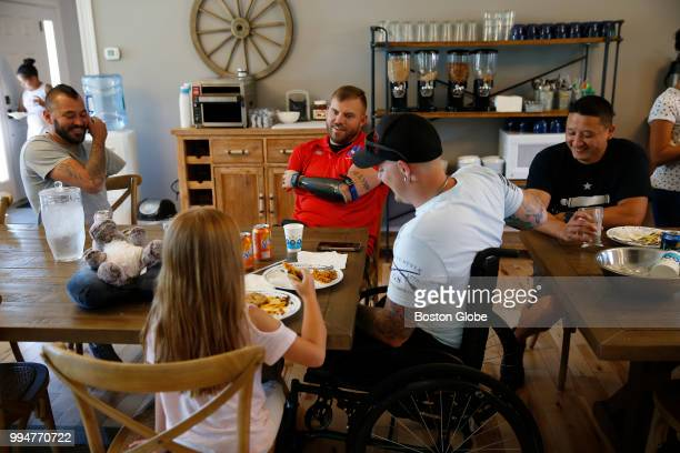 Travis Mills center shares lunch with wounded veterans and their families at the Travis Mills Retreat in Rome ME on June 26 2018 The weeklong retreat...