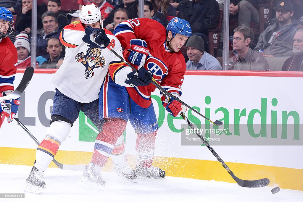 Travis Moen #32 of the Montreal Canadiens clears the puck from in front of Stephen Weiss #9 of the Florida Panthers during the NHL game at the Bell Centre on January 22, 2013 in Montreal, Quebec, Canada.