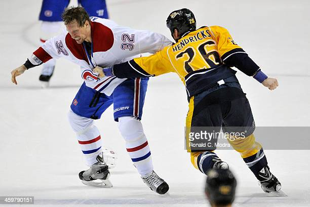 Travis Moen of the Montreal Canadiens fights with Matt Hendricks of the Nashville Predators during a NHL game at Bridgestone Arena on December 21...