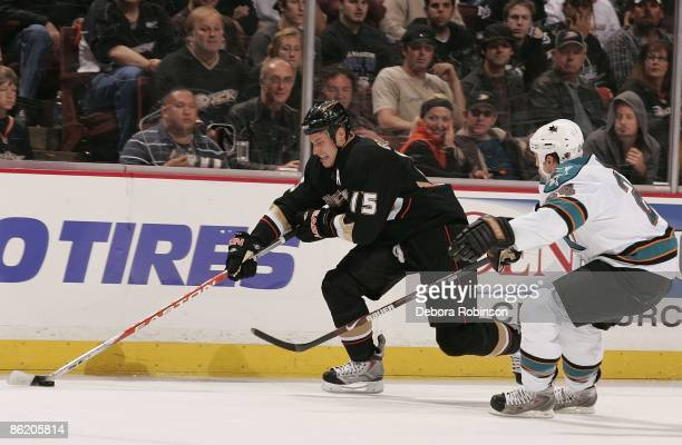 Travis Moen of the San Jose Sharks reaches around for the puck against Ryan Getzlaf of the Anaheim Ducks during Game Four of the Western Conference...
