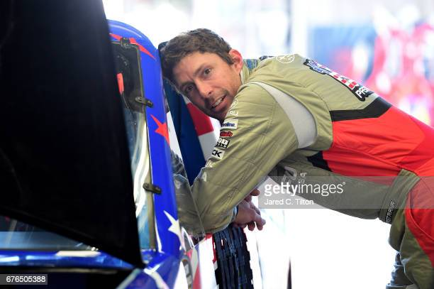 Travis Pastrana driver of the Niece Motorsports Chevrolet stands in the garage area during the NASCAR Camping World Truck Series test session at...