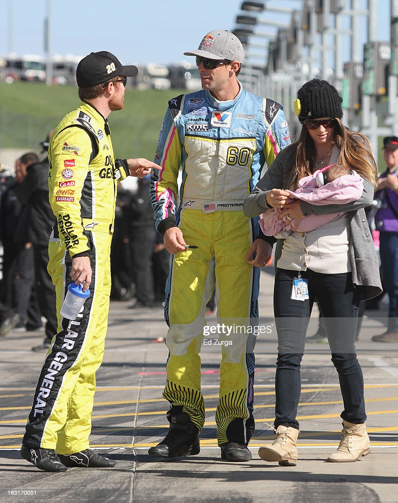 Travis Pastrana, driver of the #60 Roush Fenway Racing Ford, wife Lyn-z and daughter Addy talk with Brian Vickers, driver of the #20 Dollar General Toyota, on the grid during qualifying for the NASCAR Nationwide Series 13th Annual Kansas Lottery 300 at Kansas Speedway on October 5, 2013 in Kansas City, Kansas.