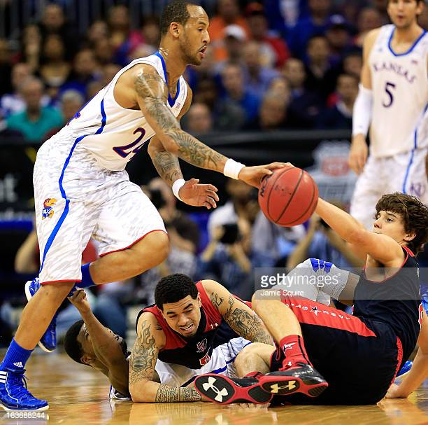 Travis Releford of the Kansas Jayhawks controls the ball as Josh Gray Dusty Hannahs of the Texas Tech Red Raiders and Elijah Johnson of the Kansas...