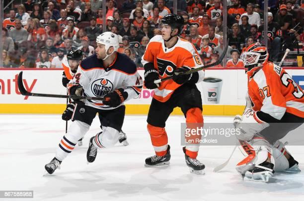 Travis Sanheim Andrew MacDonald and Brian Elliott of the Philadelphia Flyers defend Zack Kassian of the Edmonton Oilers on October 21 2017 at the...