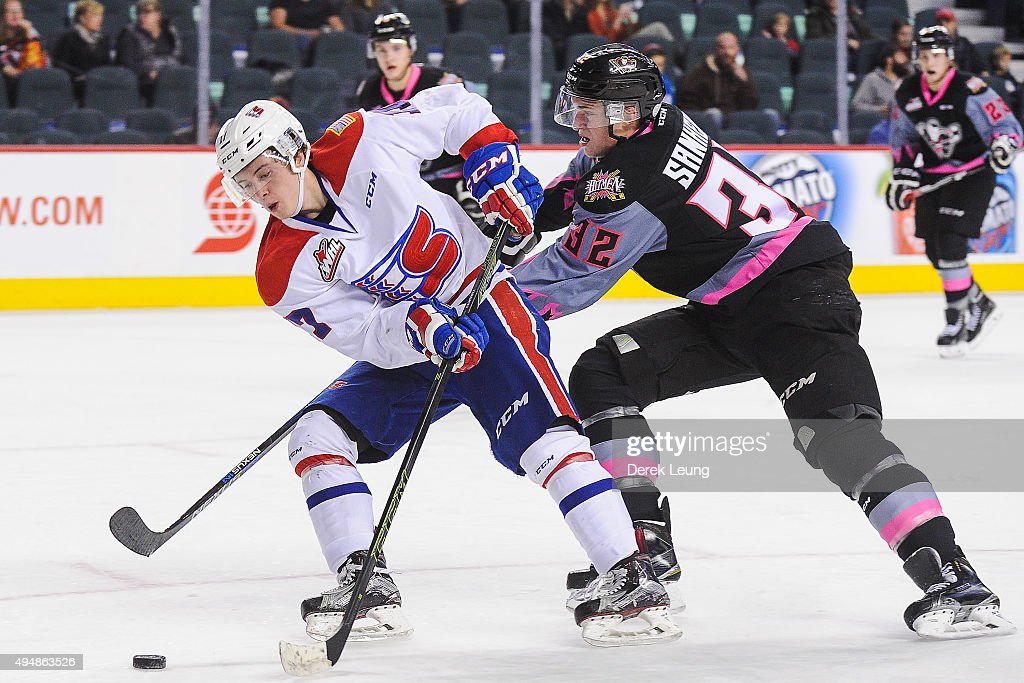 Travis Sanheim #32 of the Calgary Hitmen checks Kailer Yamamoto #17 of the Spokane Chiefs during a WHL game at Scotiabank Saddledome on October 29, 2015 in Calgary, Alberta, Canada.