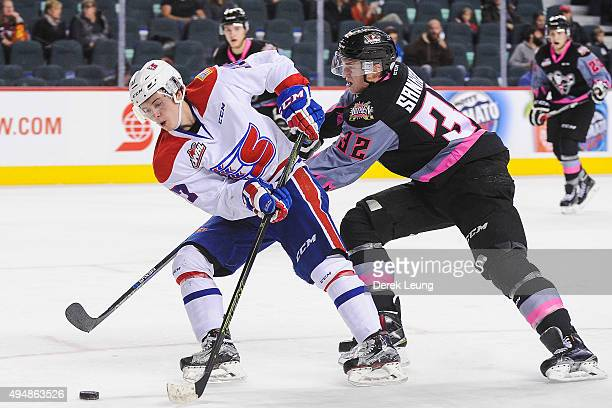 Travis Sanheim of the Calgary Hitmen checks Kailer Yamamoto of the Spokane Chiefs during a WHL game at Scotiabank Saddledome on October 29, 2015 in...