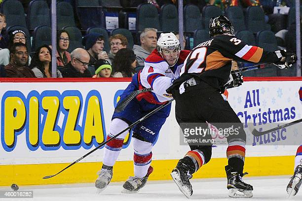 Travis Sanheim of the Calgary Hitmen gets checked by Blake Orban of the Edmonton Oil Kings during a WHL game at Scotiabank Saddledome on December 5,...