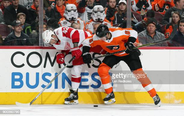 Travis Sanheim of the Philadelphia Flyers battles for the puck along the boards against Martin Frk of the Detroit Red Wings on December 20 2017 at...
