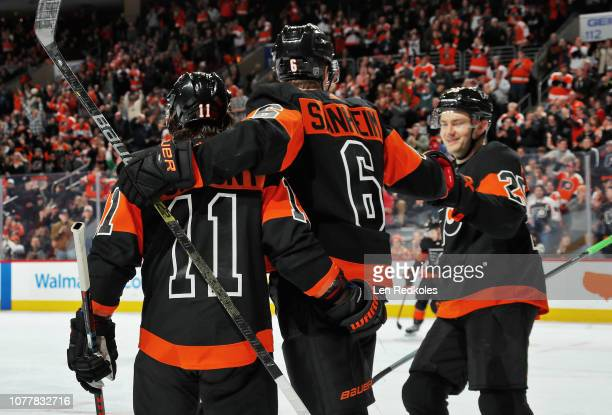 Travis Sanheim of the Philadelphia Flyers celebrates his first period powerplay goal against the Calgary Flames with Travis Konecny and James van...