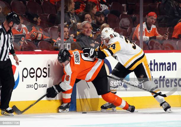 Travis Sanheim of the Philadelphia Flyers is checked by Tom Kuhnhackl of the Pittsburgh Penguins during the third period in Game Three of the Eastern...