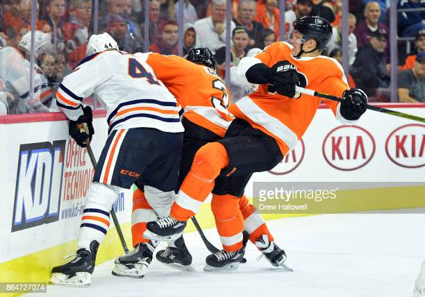 Travis Sanheim of the Philadelphia Flyers loses his balance as Zack Kassian of the Edmonton Oilers and Radko Gudas fight for the puck at the Wells...