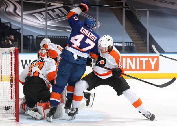 Travis Sanheim of the Philadelphia Flyers pushes Leo Komarov of the New York Islanders away form goaltender Brian Elliott during the second period of...