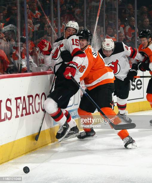 Travis Sanheim of the Philadelphia Flyers rubs John Hayden of the New Jersey Devils into the boards during the third period at the Wells Fargo Center...