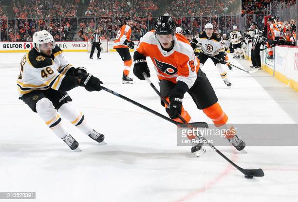 Travis Sanheim of the Philadelphia Flyers skates the puck against David Krejci of the Boston Bruins on March 10 2020 at the Wells Fargo Center in...