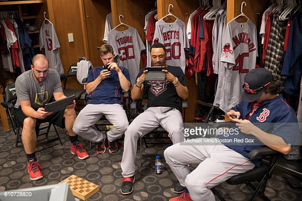 Travis Shaw Brock Holt Mookie Betts and Andrew Benintendi of the Boston Red Sox look at phones and tablets in the visitors clubhouse before a game...