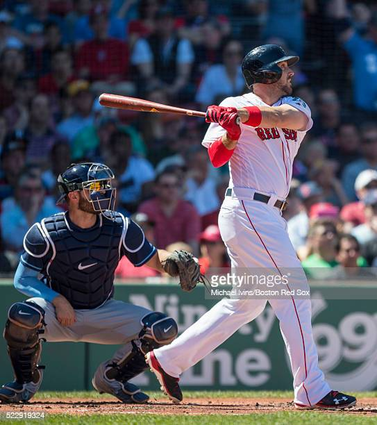 Travis Shaw of the Boston Red Sox hits an RBI double against the Tampa Bay Rays in the first inning on April 21 2016 at Fenway Park in Boston...