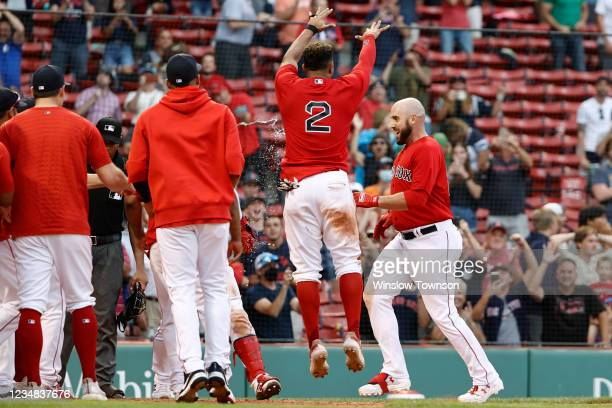 Travis Shaw of the Boston Red Sox is greeted by teammates at home plate after his game winning grand slam home run against the Texas Rangers during...