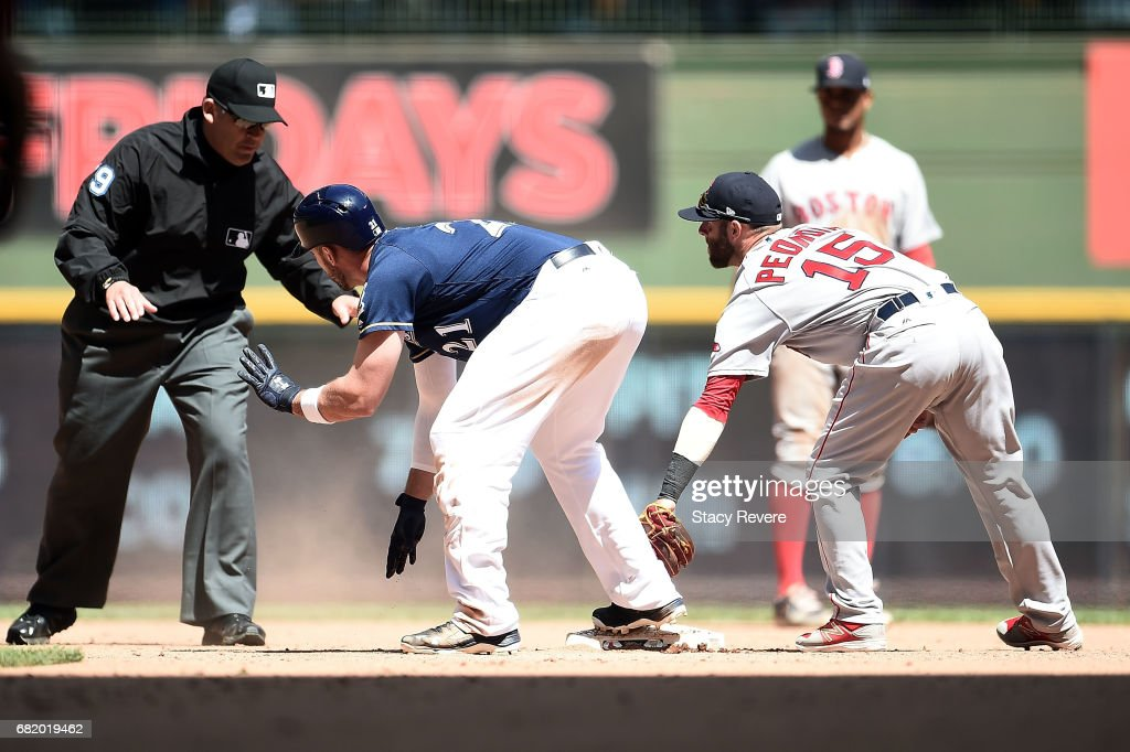 Travis Shaw #21 of the Milwaukee Brewers beats a tag by Dustin Pedroia #15 of the Boston Red Sox during the seventh inning of a game at Miller Park on May 11, 2017 in Milwaukee, Wisconsin.