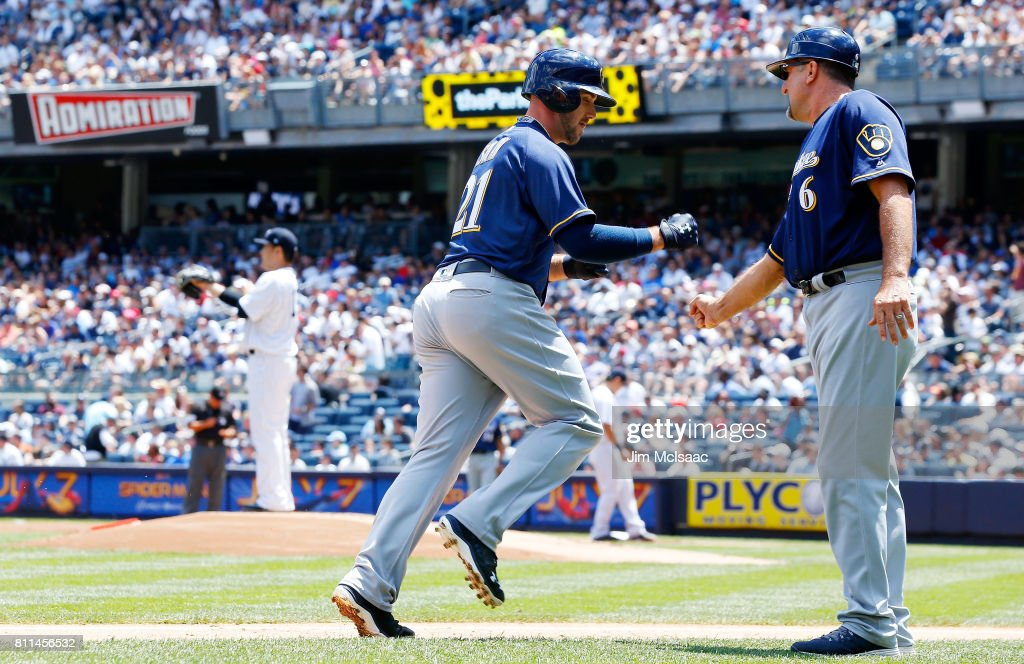 Travis Shaw #21 of the Milwaukee Brewers celebrates his first-inning, three-run home run against Masahiro Tanaka #19 of the New York Yankees with third base coach Ed Sedar #6 at Yankee Stadium on July 9, 2017 in the Bronx borough of New York City.