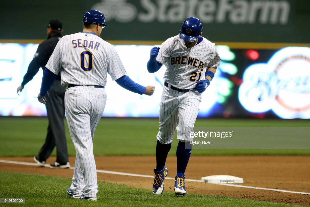 Travis Shaw #21 of the Milwaukee Brewers celebrates with third base coach Ed Sedar after hitting a home run in the fourth inning against the Miami Marlins at Miller Park on April 20, 2018 in Milwaukee, Wisconsin.