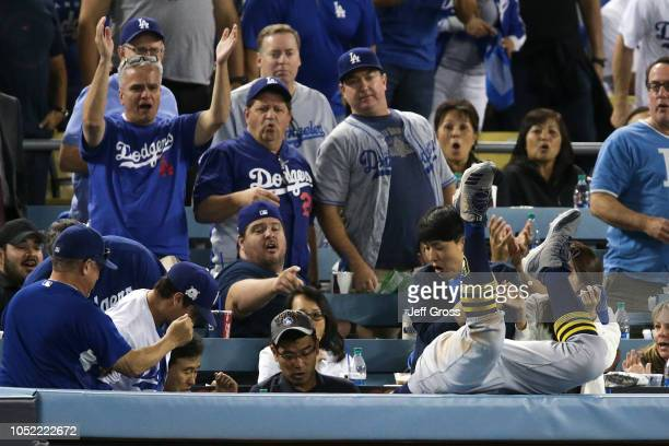 Travis Shaw of the Milwaukee Brewers falls into the stands as he attempted to make a catch on a foul ball against the Los Angeles Dodgers during the...