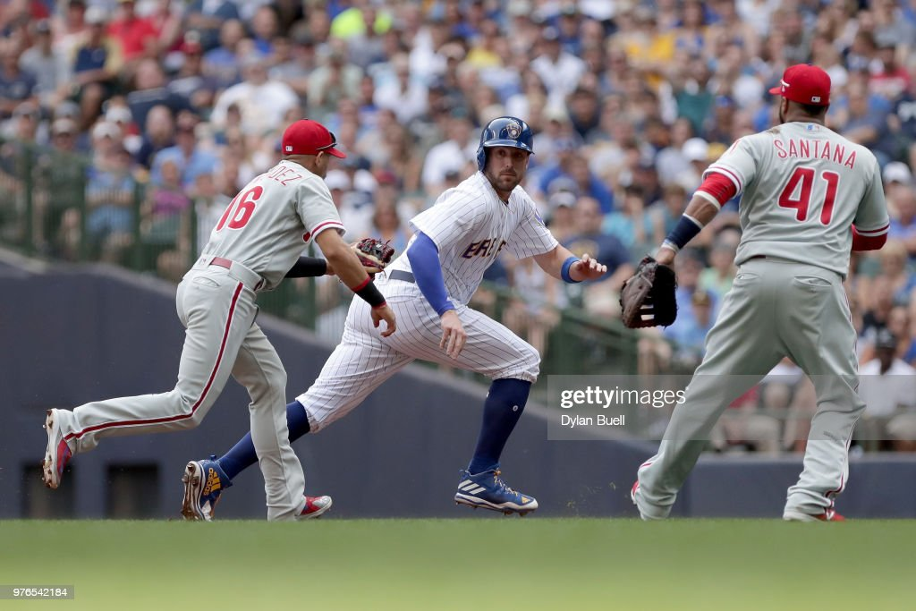 Travis Shaw #21 of the Milwaukee Brewers gets caught in a run-down between Cesar Hernandez #16 and Carlos Santana #41 of the Philadelphia Phillies in the first inning at Miller Park on June 16, 2018 in Milwaukee, Wisconsin.