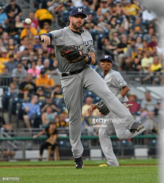 Travis Shaw of the Milwaukee Brewers throws to first base for a force out of Josh Harrison of the Pittsburgh Pirates in the third inning during the...