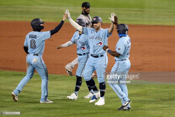 Travis Shaw of the Toronto Blue Jays celebrates with teammates after hitting the game-winning RBI in the tenth inning of an MLB game against the...