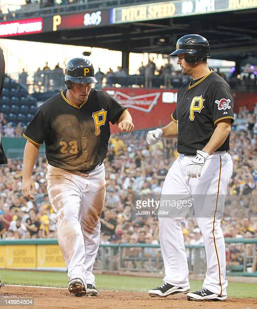 Travis Snider and Gaby Sanchez of the Pittsburgh Pirates celebrate after scoring in the third inning against the Arizona Diamondbacks during the game...