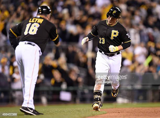 Travis Snider celebrates his solo home run with third base coach Nick Leyva of the Pittsburgh Pirates during the ninth inning against the Chicago...